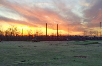 Driving range barrier netting with wood support poles