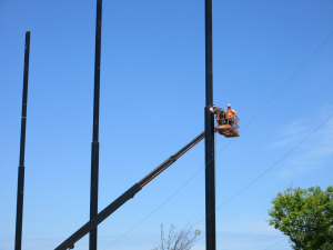 Installation crew installing cabling to support the golf netting